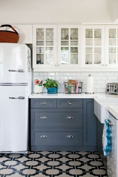 kitchen - white uppers with glass doors, blue lower cabs, white appliances, blue and beige floor