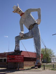 Tex Randall (Canyon, Texas)  Located on United States Route 60 to the north of downtown Canyon, this long tall Texan stands 47 feet. It was erected in 1959, and was restored in 1989. It is one of the quintessential symbols of the city of Canyon as well as the Texas Panhandle.