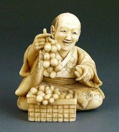 Description: Japanese carved ivory okimono depicting a gardener cutting fruit, signed Teimin, Meiji period, 4cm high
