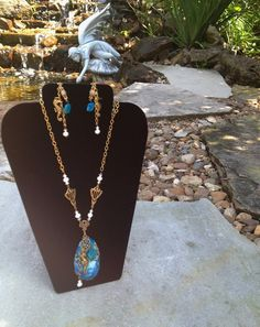 Gold set with imperial blue jasper and pearls.  Accented with cute gold seahorses!