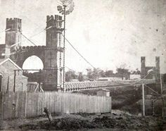 """""""This is the first known photograph of the Waco Suspension Bridge. Notice the toll keepers cottage and yard at the bottom left of the photo."""""""