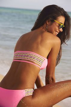 What's the bright idea for a swimsuit this season? Pops of neon and a playful Aztec print. The bandeau top is perfect for minimizing tan lines, and the details on the hipster bottoms will leave you feeling sunsational!