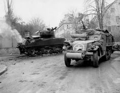 "M3A1 Half-Track of the 14th Armored Division ""Liberators"" passes close to a knocked out Sherman M4A3(76)W. The tank commander didn't make it; he's hanging half outside the turret, burned, after the German attack that destoyed his tacnk. Barr, Alsace, north-eastern France. 29 November 1944."