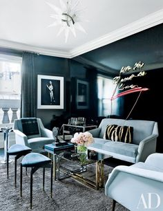 Living room with painted inky lacquered walls and a neon light