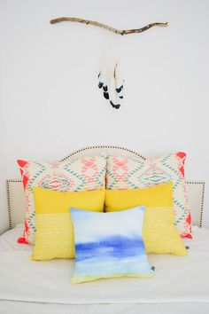 beachy bedroom, small bedroom ideas, colorful pillows, printed pillows, stylish bedding, target headboard, feather wall hanging