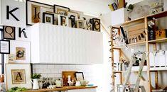Ramar med typografiaffischer i svart, vitt och beige runt ett vitt köksskåp