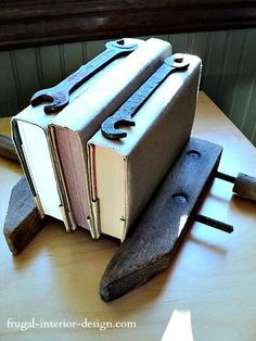 "An antique wooden vise clamps a trio of books with cool ""industrial style.""  Vintage hand tools, such as wrenches, create unique accents (displayed on book spines in this instance)."