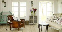 white walls; board walls; floor; dark leather; lines on sofa; aqua birdcage; cabinet by door; cutouts on folding doors; bronze light