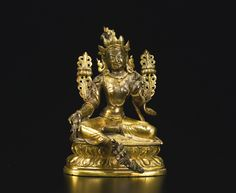 A GILT COPPER ALLOY FIGURE DEPICTING TARA TIBETO-CHINESE, 18TH CENTURY seated in lalitasana with the extended right foot supported by a lotus, wearing the five-pointed crown with curling hairstyle and decorative finial, two elaborate lotus flowers at the right and left elbows, adorned with the bodhisattva jewelry, the hem of the dhoti incised Height 4 ½ in. (11.4 cm)