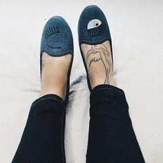 pés em cima da cama de calça jeans e sapatilha jeans com olhos pintados
