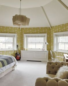 Create a sunny, cheerful bedroom with a statement yellow floral wallpaper.
