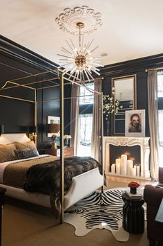 This modern bedroom design is gorgeous. Love the black walls, animal hide rug, & orb chandelier. A faux fireplace w/ candles is a lovely touch to this room's romantic decor.