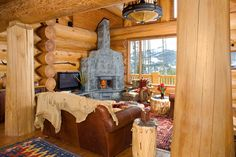 The soapstone boulders of this fireplace retain heat better than any other natural stone. Great views of the mountain bring more of the outdoors into the living room. It works beautifully. Tiny Log Cabins, Log Cabin Homes, Log Home Living, Living Room With Fireplace, Living Area, Antique Hoosier Cabinet, Cabin Office, Small Kitchenette, Wood Fuel
