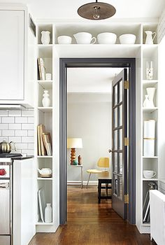 No wasted space! Built-in shelves, holding a collection of white service-ware and wooden chopping boards, frame a gray glass paned door between kitchen and living room. Design by Lauren Rubin Architecture. #Home #Storage #Bookcase #Genius