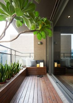Outside the living room, a beautiful covered terrace acts as a miniature backyard, complete with wooden decking and verdant plants. The built-in seating looks like a comfortable place to relax and watch as people go about their days on the streets below. Small Balcony Design, Small Balcony Decor, Modern Balcony, Balcony Plants, Balcony Ideas, Outdoor Balcony, Terrace Ideas, Small Rooftop Garden Ideas, Small Patio