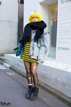 Murakami is a 23-year-old girl who easily caught our eye on the street in #Harajuku. Her look features a yellow bob hairstyle with blue lipstick, an oversized acid wash jacket (resale), a metallic clutch (from Nadia), ripped tights, a Jeremy Scott x Swatch watch & YRU platforms. #tokyofashion #street snap