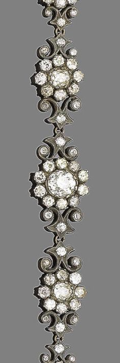 A diamond bracelet  The graduated row of old brilliant-cut diamond flowerhead clusters interspersed with similarly-cut diamond-set scrolls, mounted in silver and gold with millegrain detail, diamonds approx. 10.50ct total, Dutch assay mark, length 19.0cm. Victorian or Victorian style.