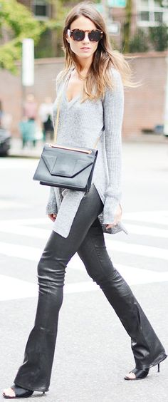 Zina Charkoplia of Fashionvibe wearing a grey V neck sweater with slit openings, leather flared pants, and black open-toe heels