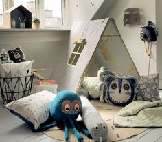 The inviting play space of a little boy's bedroom full of whimsical modern pillows and plush toys, along with a hideout.
