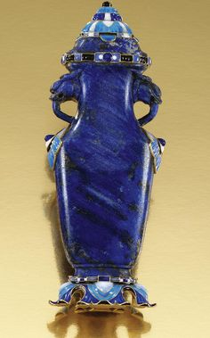 AN ART DECO LAPIS LAZULI AND ENAMEL FLASK, BOUCHERON, 1920s. Designed as a flattened amphora, its hollowed lapis lazuli body applied with handles carved to depict two dragons, its lid, base and sides further embellished with stylised three tonal enamel motifs, measurements approximately 120mm x 51mm x 32mm, signed Boucheron Paris, maker's marks and French assay marks. #ArtDeco #Boucheron #flask