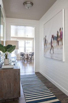 Long cottage foyer features white shiplap clad walls lined with a Thom Filicia Warm Memories ...