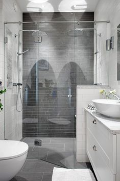 Bath - Grey tiles in an extraordinary two-person shower, the star of this room, is complemented by the Carrera marble countertop & white vessel sink.
