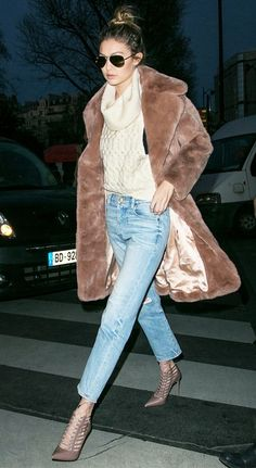 Gigi Hadid wears a chunky turtleneck, furry coat, cropped jeans, and lace-up pumps