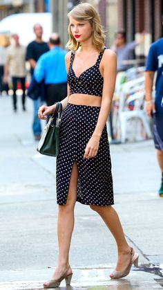 STREET STYLE JULY 7, 2014 Swift stepped out in New York City in a black-and-white polka dot bralette crop top and skirt combo, which she styled with a green Kate Spade bag, retro heels, and her signature bold red lip.