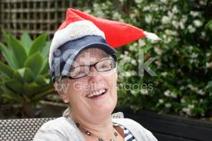 A Senior Lady laughs to the camera as she pops her Santa hat on top. Interracial Marriage, Kiwiana, Christmas Background, Santa Hat, Image Now, Royalty Free Stock Photos, Women Wear, Framed Prints, Lady