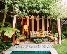 A striped cabana and green patio furniture in an outdoor living space