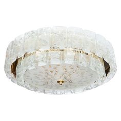 Two-tier brass flush mount fixture composed of multiple molded glass elements by Doria.
