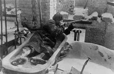 A Russian soldier firing from a frozen bath tub in Stalingrad.