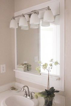 DIY Pottery Barn -Inspired Bathroom Mirror on a Budget.  Nice way to dress up a standard mirror above sink.