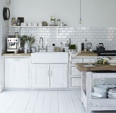 Subway tiles, farmhouse sink and rough cut butcher block counters and island...so simple and pretty.