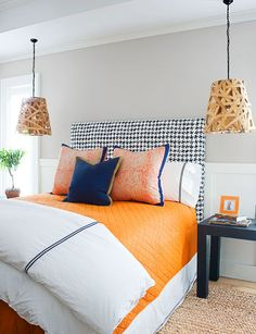Update the classic blue-and-white combo with a tangy orange. Dramatic pendant lights also free up storage space on the bedside tables.