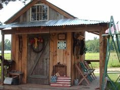 my tack room, my awesome husband built me this tack room!from scrap wood and metal. A reclaimed old barn door cut to fit- an cozy covered porch with painted chairs to set and watch the horses run..and a hitchin post. And I decorated it with old horse tack and filled it with new horse tack...what an awesome space for only a couple hundred bucks! thanks hun!, Yards Design by madelyn