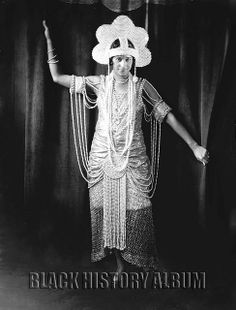 Full-length female portrait of an African American showgirl wearing an  unusual art deco inspired dress and headpiece with intricate pearl  bead work. Photograph by Addison N. Scurlock, 1920s.