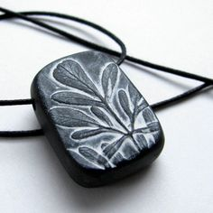 """""""A sweet little rue leaf stand out on black polymer clay and durable white acrylic paint is applied. The effect is the feel of a dark frosty night.""""  by etsy artist UnaOdd  ... cool idea!"""