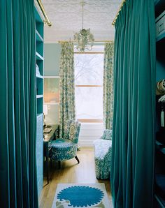 Love this luxe looking little dressing room with its grand blue curtains that hide storage and closet space.