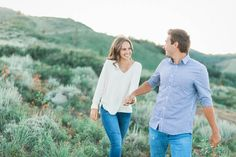 What to wear for engagement photos. Casual outfit for engagement. Mountain wildflowers. couple holds hands and walks smiling. Engagement photo ideas. www.gideonphoto.com