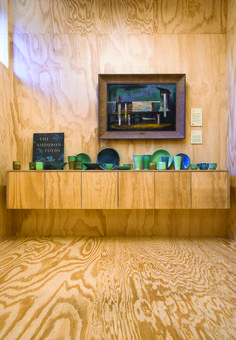 """On the custom-designed plywood wall-hung cabinet is a collection of Shearwater pottery; above hangs Tower and Surf Boards, 1952, by Davis Miller (1917– 2012), PVAC's 1952 """"Purchase Prize"""" winner."""