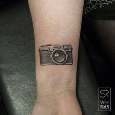 Tiny wrist camera tattoo.