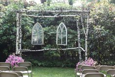 Gothic windows hung from a birch canopy create a chapel for an outdoors wedding