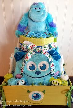 This Monsters Inc. diaper cake is loaded with usable goodies including a Mike Wazowski tied storage bin, a large plush Sully hooded towel, an extra large Disney receiving blanket, a plush Sully, Sully and Mike pacifiers, 6 Monsters Inc washcloths, baby toiletries, socks and of course diapers!!!! Made by 209 Diaper Cakes & Gifts - facebook.com/209diapercakes
