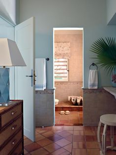 View the tropical dressing room and walk-in shower decked in terra cotta tile and a moisture-resistant Roman shade on HGTV.com.