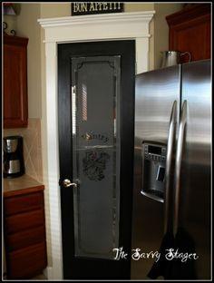 Black pantry door with great molding.