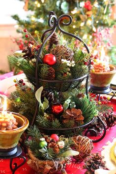 Wrought iron tier bowl filled with greens, ornaments and pine cones