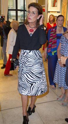 Princesa Carolina de Mónaco Acto: Inauguración de una exposición en la Galería Adriano Ribolzi (Mónaco). Fecha: 15 de septiembre de 2016. 'Look': Carolina de Mónaco optó por una blusa negra con escote 'V', que combinó con una falda de 'animal print' y 'pepe toes' al tono de su blusa. Como complementos, lució un collar de dos piedras en negro y rojo y dos brazaletes en tonos marrón, dorado y blanco.