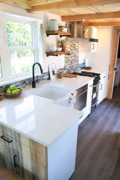 The kitchen is equipped with an L-shaped solid surface counter, tile backsplash, farmhouse sink, full size propane range, dishwasher, and full size refrigerator.