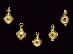 FIVE GREEK GOLD AND GARNET POMEGRANATE PENDANTS  HELLENISTIC PERIOD, CIRCA 2ND-1ST CENTURY B.C.  Each a hollow sphere with three equidistant bezel-set pointed garnets, the bezels encircled by granulation, a pyramid of three granules between, the underside with the pomegranate calyx formed of sheet, the suspension loop joined to the sphere by a biconical collar